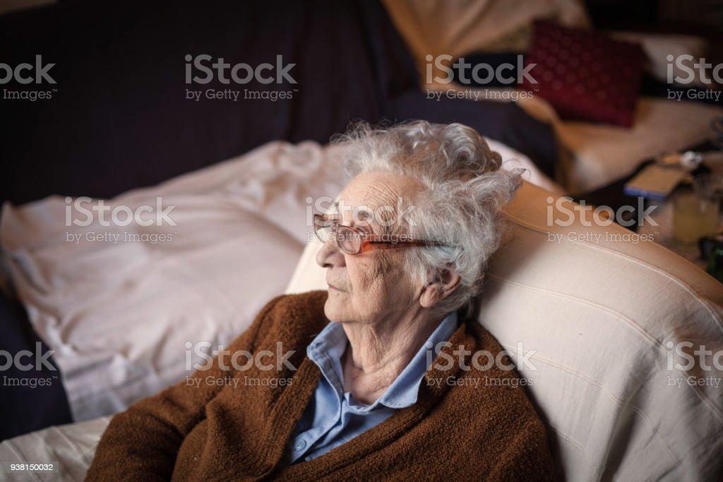 Senior woman relaxing,sitting on sofa.