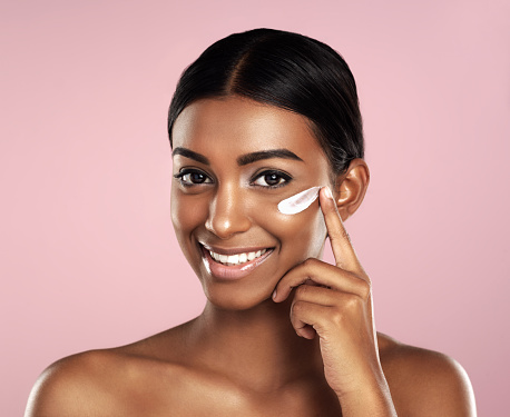 Studio portrait of a beautiful young woman applying moisturizer to her face against a pink background