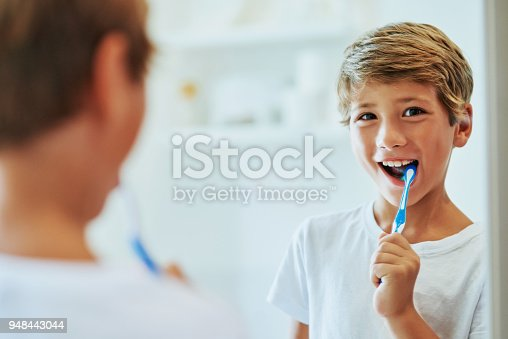 Shot of a cheerful young boy looking at his reflection in a mirror while brushing his teeth in the bathroom at home during the day