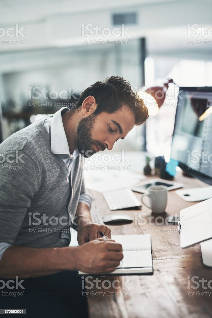 Keeping notes as he stays on top of his work stock photo