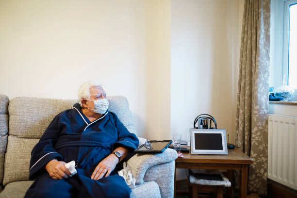 Keeping Others Safe An elderly man sits looking out of the window as he sits alone with a protective face mask on. one senior man only stock pictures, royalty-free photos & images
