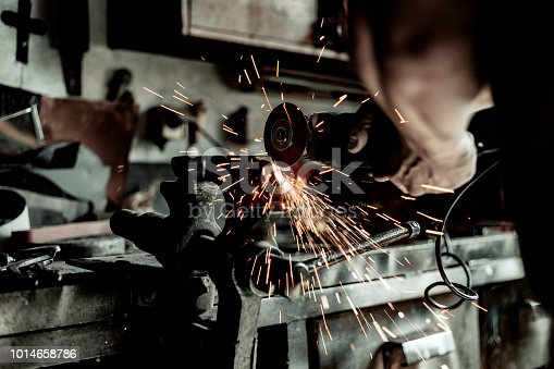 Electric Wheel Grinding on Steel Structure in Factory. Sparks From the Grinding Wheel. Worker Cutting Metal With Grinder. Sparks While Grinding Iron. Metalworking Industry Concept. Craftsman Worker in His Workshop Working on His New Project.