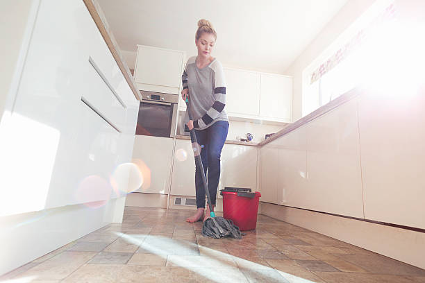 Keeping the Kitchen Sparkling Clean One woman mopping the floor in her kitchen. mop stock pictures, royalty-free photos & images