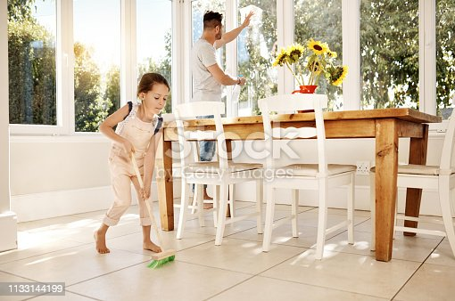 Shot of a father and his little daughter doing chores together at home