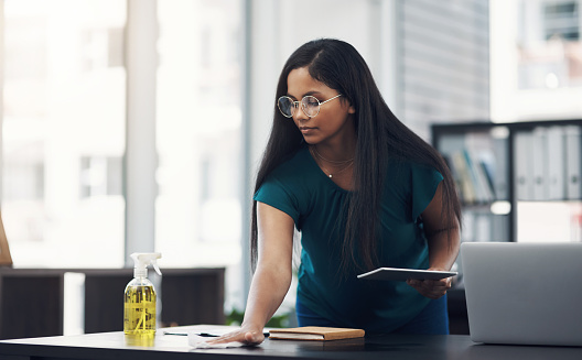 Shot of a young businesswoman cleaning a workspace in an office
