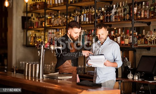 Shot of a bar manager and bartender checking the stock in the pub