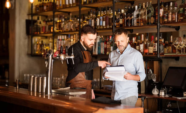 Keeping track of the stock Shot of a bar manager and bartender checking the stock in the pub bartender stock pictures, royalty-free photos & images