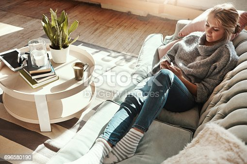 Shot of a young woman relaxing on the sofa at home and using a mobile phone