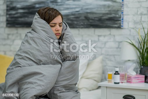 A young caucasian woman is in bed on a sick day. She is curled up in a blanket,.