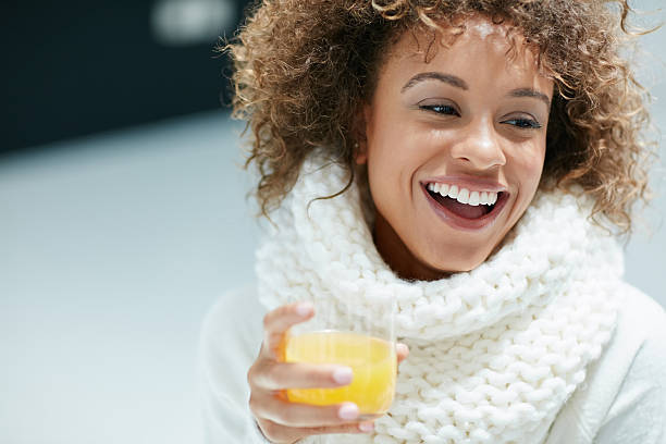 keeping winter colds and flu at bay the citrusy way - drinking juice stock photos and pictures