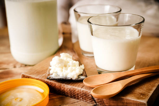 Kefir Grains In Wooden Spoon With Glass Of Kefir stock photo