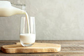 istock Kefir, milk or Turkish Ayran drink are poured into a glass cup from a bottle. A glass stands on a wooden stand on a rustic wooden table. Place for text 1198789194