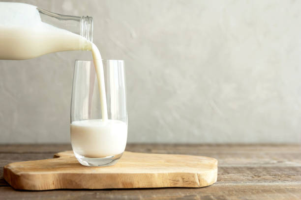 kefir, milk or turkish ayran drink are poured into a glass cup from a bottle. a glass stands on a wooden stand on a rustic wooden table. place for text - white background стоковые фото и изображения