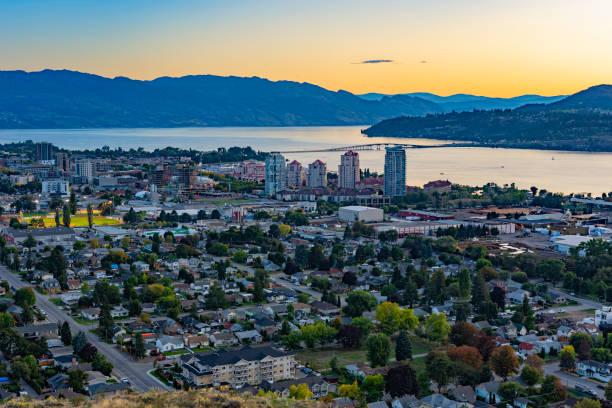 Kelowna British Columbia and Okanagan Lake from Knox Mountain at sunset A view of Kelowna British Columbia skyline and Okanagan Lake from Knox Mountain after sunset british columbia stock pictures, royalty-free photos & images