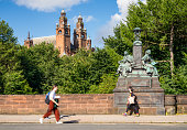 Glasgow, Scotland - People crossing Kelvin Way Bridge in Glasgow's West End, with the towers of Kelvingrove Museum and Art Gallery on the horizon.