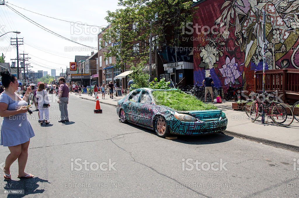 Kensington Market: Unidentified people and a car with plants inside stock photo