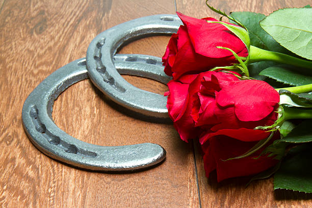 Kentucky Derby Red Roses with Horseshoes on Wood stock photo