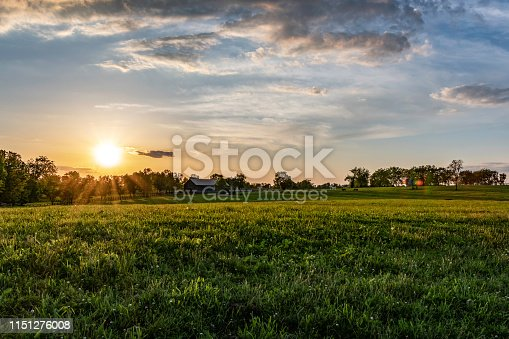Kentucky horse farm at sunset on a spring evening. Barn and horses grazing at the far end of the bluegrass pasture lit with golden hour sunlight.