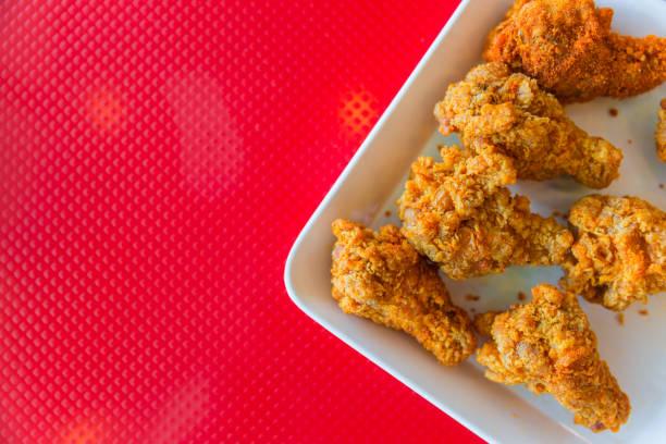 estilo de kentucky frango sobre fundo vermelho, com espaço para texto - junk food - fotografias e filmes do acervo