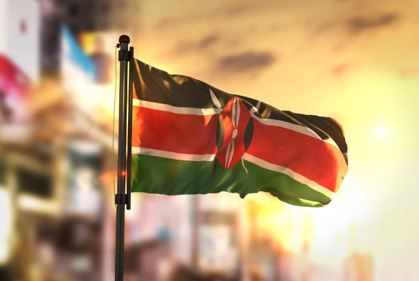 kenya flag against city blurred background at sunrise backlight - kenya stock photos and pictures