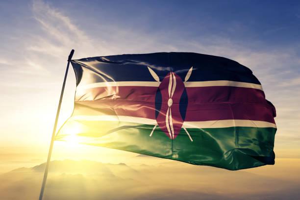Kenya Kenyan flag textile cloth fabric waving on the top sunrise mist fog stock photo