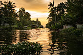 kerala backwaters scenery at sunset with water canal and houseboat, with warm light and palm trees