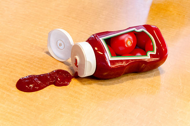 ketchup bottle with messy spill and tomato label - ketchup bottle stock photos and pictures