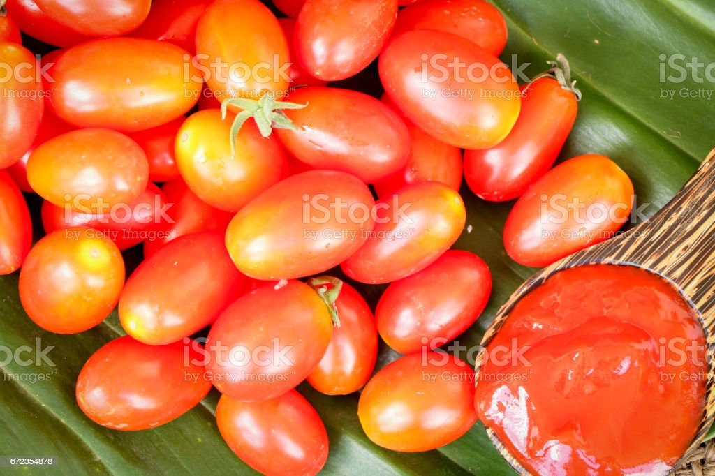 ketchup in spoon with tomatoes stock photo