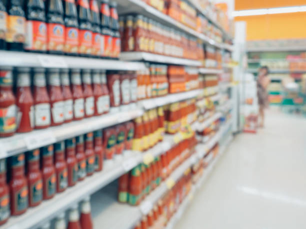 ketchup sauce seasoning bottles products in supermarket shelves blurred background stock photo