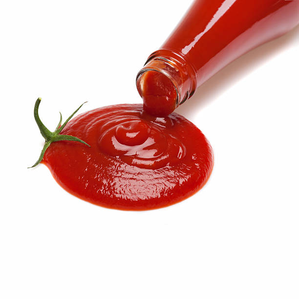 Ketchup tomato Ketchup is poured from a bottle in the shape of a tomato. ketchup stock pictures, royalty-free photos & images