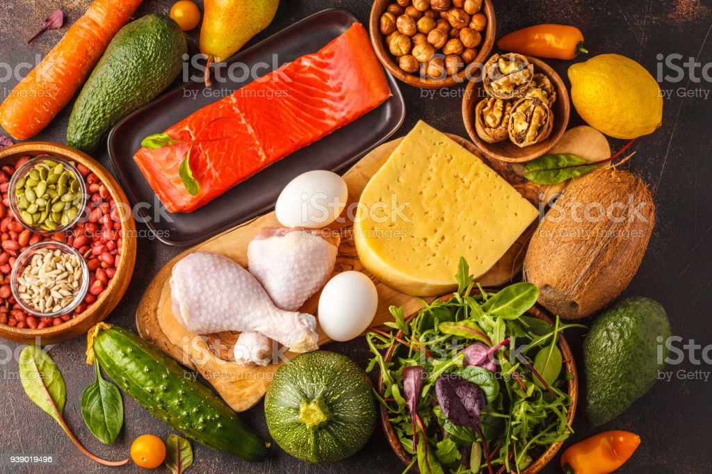 Keto (ketogenic) diet concept. Balanced low-carb food background. High protein food. Vegetables, fish, meat, cheese, nuts on a dark background. stock photo