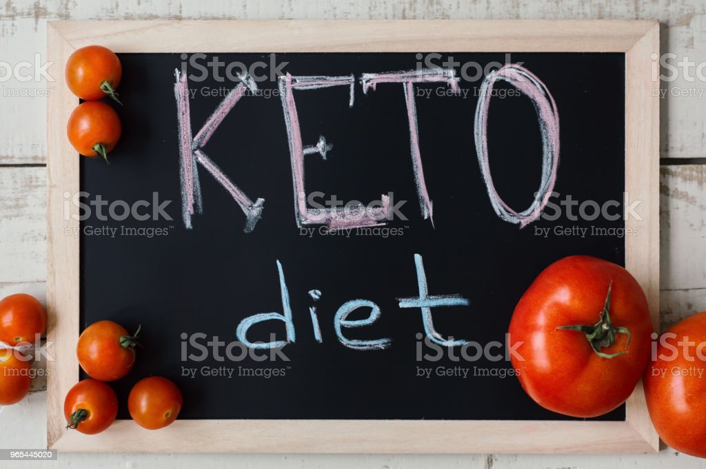 Keto diet concept. Ketogenic nutrition. Blackboard with handwritten text 'Keto Diet', red fresh tomatoes on wooden background, top view zbiór zdjęć royalty-free
