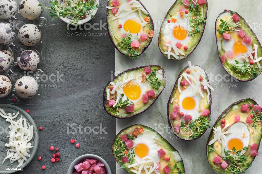 Keto diet dish: Avocado boats with ham cubes, quail eggs, cheese and cress sprouts - Royalty-free Above Stock Photo
