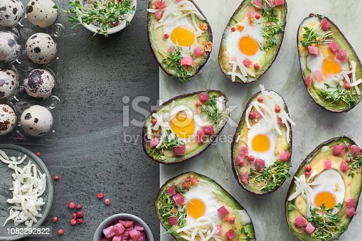 Keto diet dish: Avocado boats with ham cubes, quail eggs, cheese and cress sprouts on stone serving board
