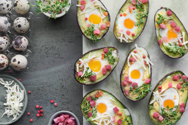 Keto diet dish: Avocado boats with ham cubes, quail eggs, cheese and cress sprouts stock photo