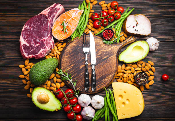 Keto diet foods Knife and fork over wooden cutting board and ketogenic low carbs ingredients for healthy eating concept and weight loss, top view. Keto foods: meat, fish, avocado, cheese, vegetables, nuts ketogenic diet stock pictures, royalty-free photos & images