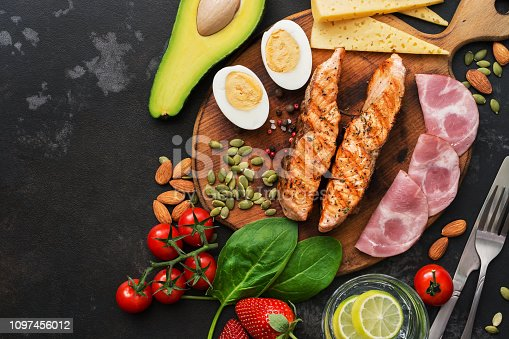 istock Keto lunch or dinner - grilled salmon, vegetables, boiled egg, water with lime, nuts, ham and cheese on a dark background. Ketogenic diet concept. Top view, copy space. 1097456012