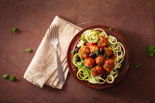 keto paleo zoodles zucchini noodles with meatballs and olives - paleo diet stock photos and pictures