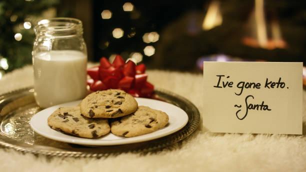 """ketogene weihnachten: santa weigert sich höflich milch und kekse mit einem """"ich bin gegangen, keto"""" zettel am kamin am heiligabend - low carb kekse stock-fotos und bilder"""