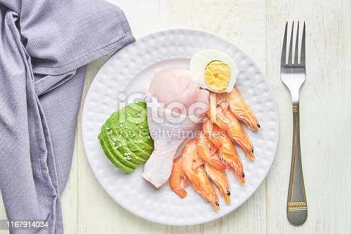 1129572695 istock photo Ketogenic diet concept. A set of products for low carb keto diet. Green avocado, sesame, chicken leg, eggs and shrimps. Healthy food concept. 1167914034