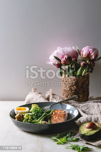 Ketogenic low carb diet dinner grilled salmon, avocado, broccoli, green bean and soft boiled egg in ceramic bowl served with olives and nuts, bouquet of peonies on grey table.