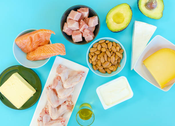 Ketogenic diet food. Low-carb food background, fish, meat, cheese, nuts, oil and butter on a blue background. mockup,  flatlay, flat lay Top view Keto diet concept. stock photo