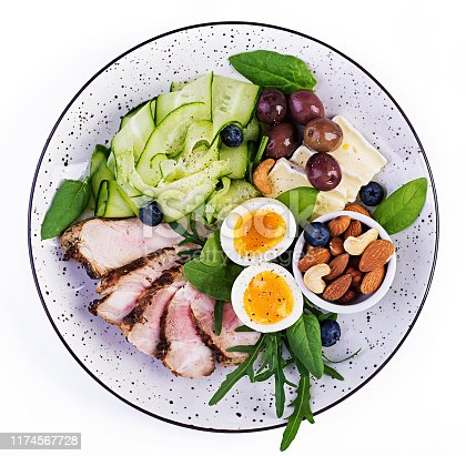 Ketogenic diet. Keto brunch. Boiled egg, pork steak and olives, cucumber, spinach, brie cheese, nuts and blueberry. Top view