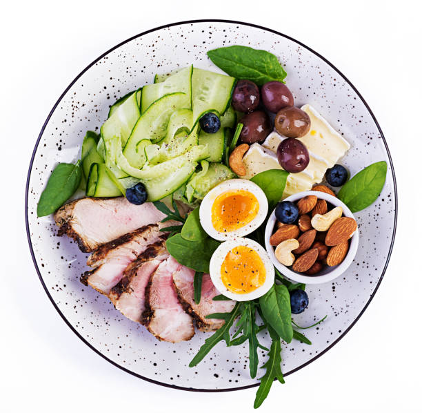 Ketogene Ernährung. Keto Brunch. Gekochtes Ei, Schweinesteak und Oliven, Gurke, Spinat, Brie-Käse, Nüsse und Heidelbeere. Ansicht von oben – Foto