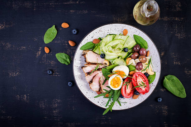 Ketogenic diet. Keto brunch. Boiled egg, pork steak and olives, cucumber, spinach, brie cheese, nuts and tomato. Top view stock photo