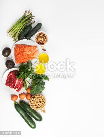 Ketogenic, keto diet, including vegetables, meat and fish, nuts and oil isolated on white background, vertical with copy space