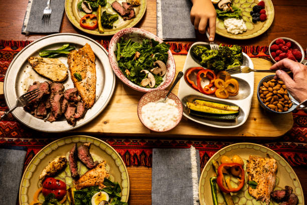 A ketogenic meal laid out on a dining table with the hands of people serving themselves stock photo