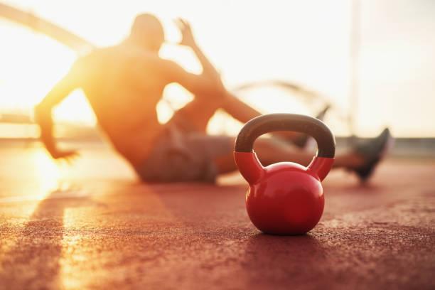 kettle bell in focus, fitness training at early morning. - training imagens e fotografias de stock