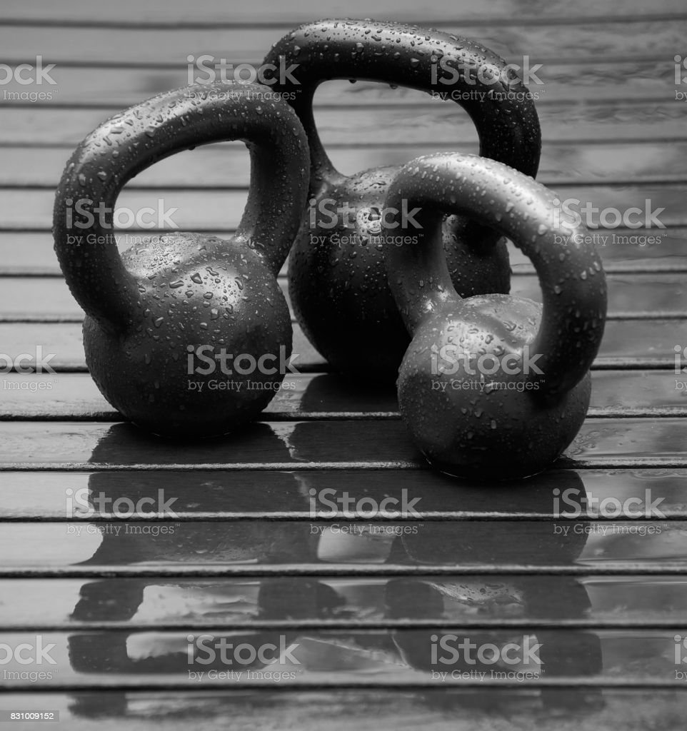 Kettle weights in the rain on some floorboard outside, beaded water running on the metal, in black and white for drama stock photo