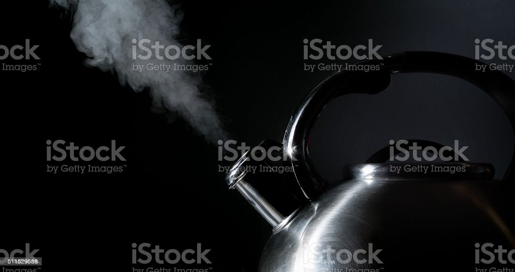 kettle whistling, boiling kettle, steam, on a black background stock photo